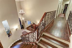Upstairs landing is a continuation of uncompromising quality with curved walls, hardwood floors, wood tread staircase and ornate wrought iron balustrade.