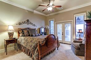 Wall of windows provides serene vistas in this finely appointed secondary bedroom with crown molding, ceiling fan, crown molding and lush carpet.