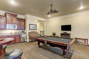 Expansive game room with a mini-kitchen including an icemaker, is ideal for enjoying the company of friends and family.