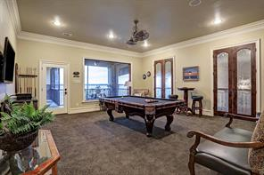 Ample natural light glistens in the game room thanks to banks of windows and French doors to Juliette balcony overlooking Living Room.  Access door leads to screened in porch area with outdoor fireplace.