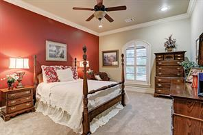 Well-appointed secondary bedroom boasts lush carpet, crown molding and ceiling fan.