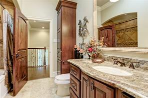 30.  Beautiful secondary upstairs bath boasts rich mahogany cabinetry and granite counter tops.