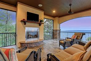 Serenity and gorgeous views envelope the upstairs patio where a fireplace serves as the focal point.