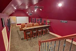 Sunken theatre room boasts 7 recliners, ceiling fan and recessed lighting.