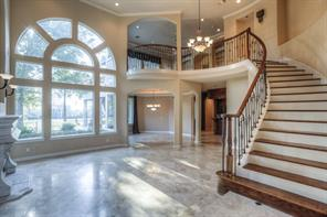 From the entry is a two-story living space with a curved staircase trimmed in stained wood. The large, custom window lets in light and gives a view of the golf course beyond.
