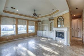 The family room has 3 large windows that overlook the golf course. Built-ins house your entertainment equipment and keep it organized. Note the wall of storage cabinets beyond.