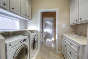 Laundry room with sink and an additional separate office or craft area beyond.