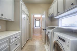 Laundry area has plenty of storage and access to the backyard from the door beyond.