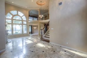 The two-story entry with marble floors opens into the living room.