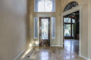 Two-story entry with leaded glass door and marble floors. Office just off of the entry with custom half moon window transom.