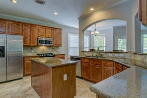 The kitchen has plenty of cabinets, granite countertops, an island and the refrigerator stays.