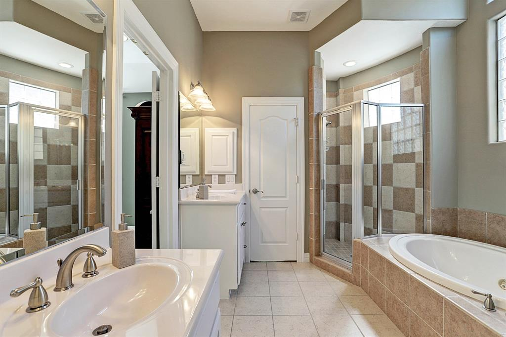 Master bathroom with two vanities, two closets, jacuzzi tub and shower