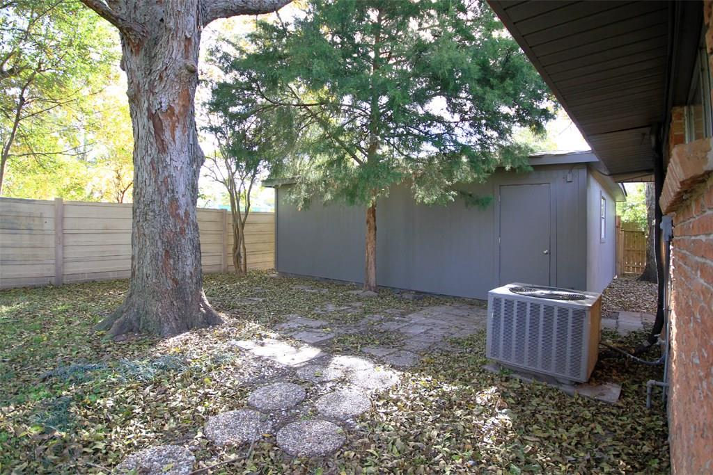 Large fenced backyard with mature trees and entrance to the two car garage