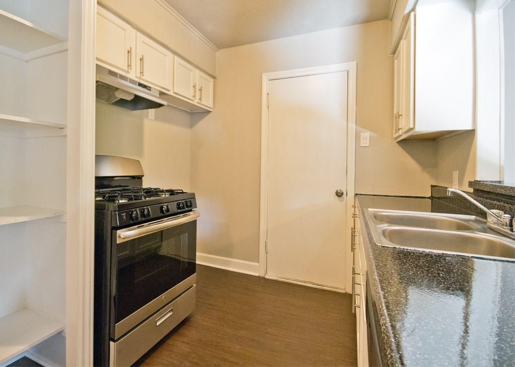 Bright kitchen features a dishwasher and new range/oven and range hood. Door leads to rear mudroom and laundry