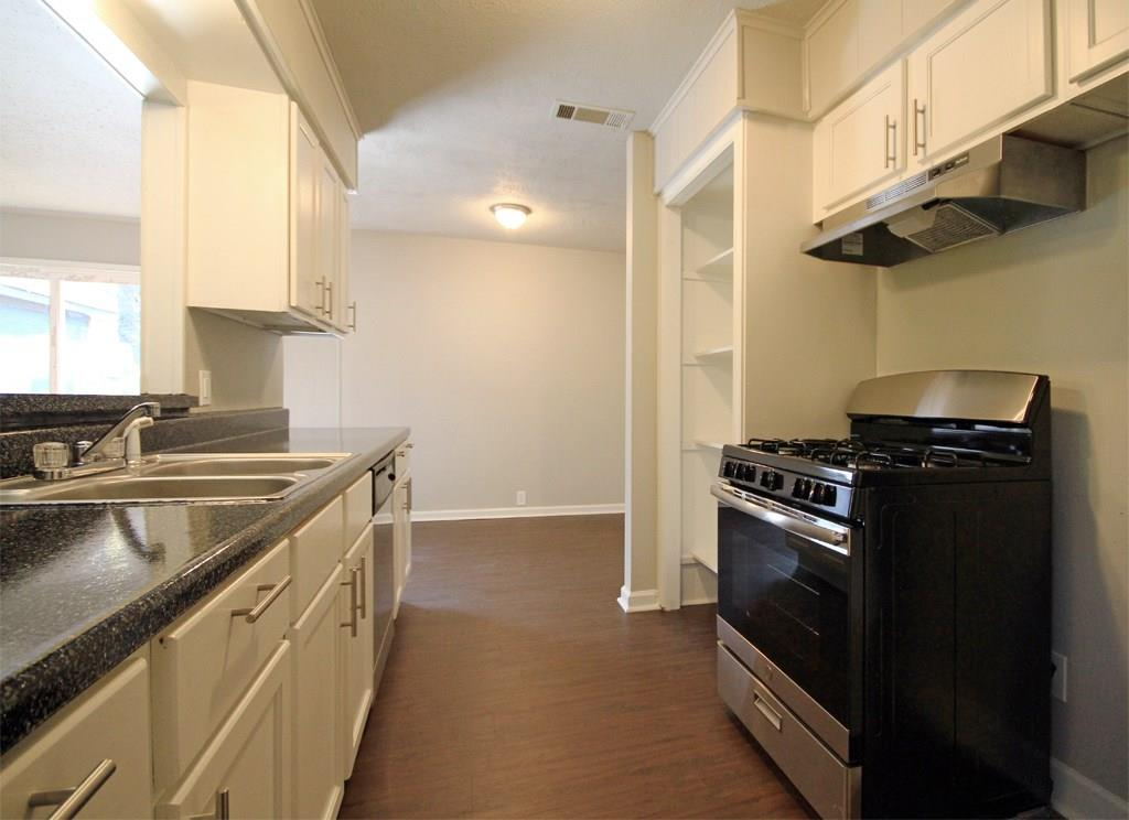Galley style kitchen opens up to living room and breakfast bar for entertaining. Large built in pantry provides plenty of storage