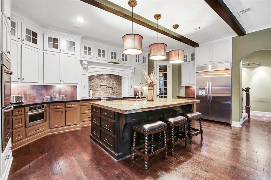Spectacular 1.5 story, 4 bedrooms with extra room and a study! Master and 2 additional bedrooms down stairs. All floors down are hand-scraped wood and tile with high ceilings. Study and extra room down stairs. Fantastic utility room with folding area and wash sink. Island kitchen with Serengeti granite counters, pot filler and unique copper accents. Tons of built-ins. One spacious bedroom with full bath upstairs. Gorgeous curb appeal with landscape lighting, sprinkler system and automatic driveway gate. Huge lot, just over an acre! Beautiful backyard with outdoor kitchen. 3 car garage with great workshop.