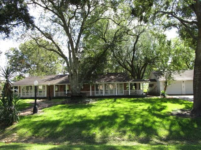 HomePath offers you this lovely sprawling home on close to 1 acre of land in sought after Bluebonnet Hills. This land is graced with many mature oak shade trees! The house sits back on the lot to give it a plantation look. The restful front porch goes the full length of the front of the house, so fill it with quaint rockers and enjoy time with friends and family. This home has a grand den with rock fireplace. The cute breakfast area has plenty of natural light.  The kitchen has ample counterspace, but is compact enough not to wear you out cooking. There are 2 masters in this home. One has a wall of windows and quick access to the garage, the other is closer to the secondary bedrooms, in case you need to be close to the kids. Come out to the backyard haven and you get a covered patio and to the far left is a versatile man cave, workshop, additional garage or kid play room.  You really need to see this house and make it yours. You will be close to I-10 and shopping.