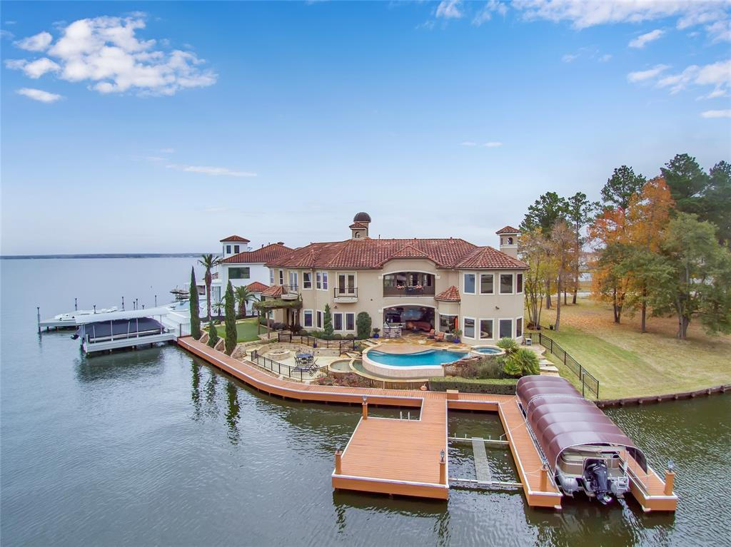 Breathtaking waterfront home on Lake Conroe with over 150 feet of bulkhead.  Located in Water Oak a gated community.  This home offers a master suite with heated bath tile floors, a guest bedroom with private bath, a study and another full bath all down.  Additional 3 bedrooms, 3 1/2 baths along with a game room, gas fireplace and bonus room up.  Grand 2 story entry with a formal living/dinning area and gas fireplace.  Family room and another gas fireplace and kitchen with bar down.  Plenty of views of the Lake.  An attached 4 car garage for lots of space.  Exterior includes Saltwater Pool, 1 covered Boat Slip, and 1 slip for jet ski or additional boat, Putting Green, Gas Fire-pit, Outdoor Kitchen and Patio.  Interior features include travertine flooring, granite counters, custom window treatments, built-in's, surround sound, wine closet, and butler's pantry.