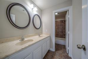 Upper full bath with two sinks, marble counters and private shower area.