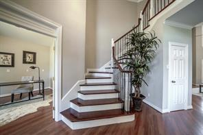 Beautiful new crafted stairway has new railing and iron balusters! Coat closet shown in this shot.