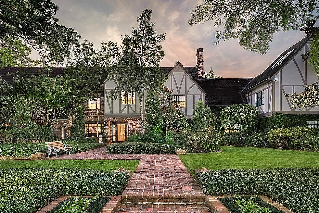 Defined by its elegant Tudor architecture, this River Oaks home boasts 5 bedrooms and multiple living areas with soaring ceilings. The third story loft includes a full gym and sauna. The resort-style property offers a pool, tennis court, putt putt course, summer kitchen with wet bar, and accommodations for 9 cars. With over 50,000 square feet of lot space in this prime location in Tall Timbers, you'll never have to leave this when you have a country club right in your own backyard!