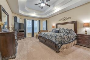 Large master suite with tiered ceilings and additional space for a seating area.