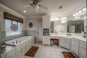 Master bath has optimal lighting, full size jetted tub, 2 sinks, a shower and a vanity area. It is tiled and has a ceiling fan and huge closet.