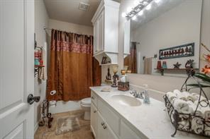 Extra bathroom with storage cabinet and marble counter, tile floors.