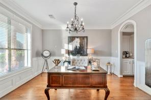 Bright study with wood floors, crown molding, wainscoting, and casings.