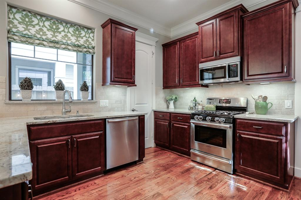 Dark-stained cabinets, stainless everywhere and luxurious granite. Come see this kitchen!