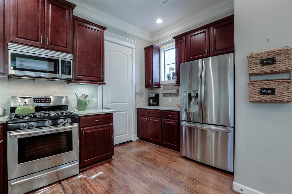 Great alternate view shows the kitchen's substantial storage space and awesome refrigerator. Door leads to the 2 car garage.