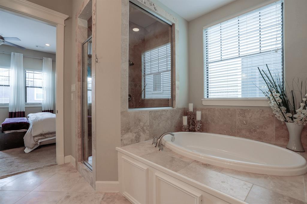 Full view of the master tub and large window above it. Leads back towards bedroom.