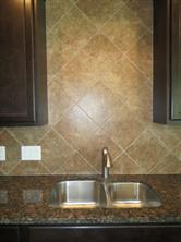 Ceramic Tiled Backsplash and Stainless Steel Sink in Kitchen