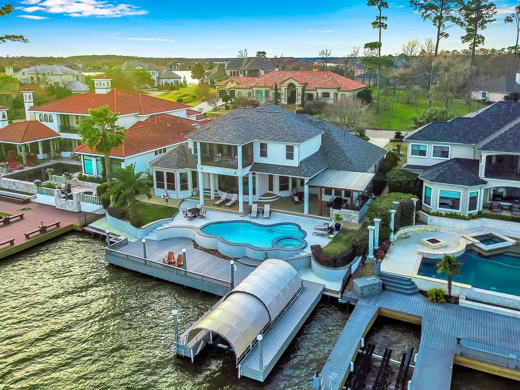 Breathtaking southeast waterfront home located in the Estates of Bentwater. Inspiring 7-mile open water views across back of home. Abundant outside living area w/ pool/spa, grand summer kitchen, covered patio, dock, boat slip/lift & new bulkhead 2012. 4 BR (2 masters suites down & 2 up), 5 baths (incl. a pool bath), formal Living & Dining, Media & Game RM w/ screened balcony. Handsome study w/built-ins & French doors. Spacious master suite sitting area, lrg closet (connects to laundry) & updated master bath. Kitchen has center island w/ all Jenn Air Professional Stainless appliances. 2 gas fireplaces; 13KW gas generator; oversized 3 car garage w/ golf cart bay. This  does not come along every day! Grand Pines membership available. Come to the lake community of Benwater for the Lifestyle! Play 54 holes of golf, swim in 2 sparkling pools, enjoy the tennis courts, sports center, marina, yacht club, park with playground & 24-hr secure manned gated access.