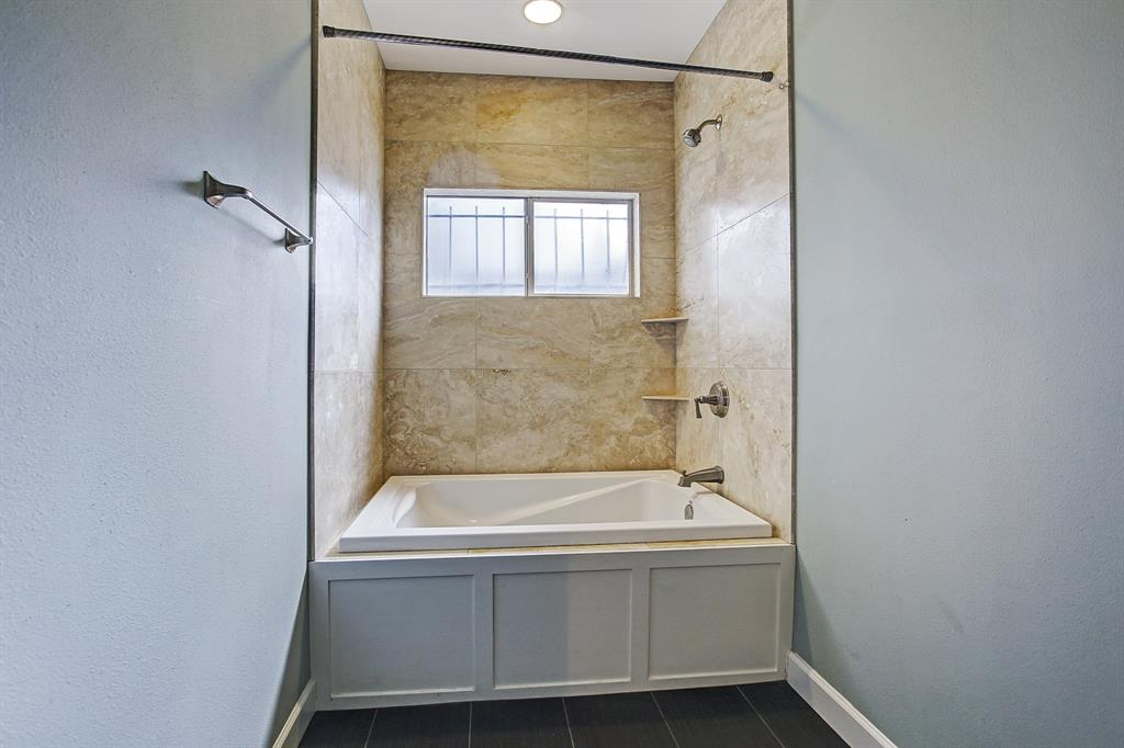 Tub/Shower combination with tile to the ceiling in the flrst floor bathroom. Natural light flows into this space.
