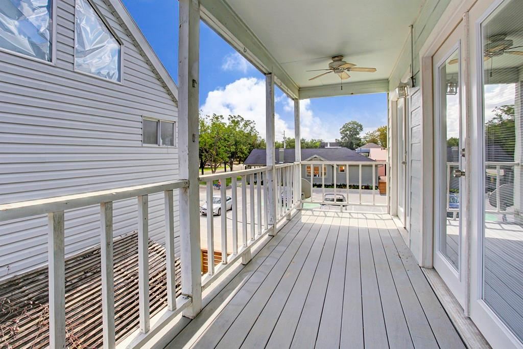 Long, covered porch overlooks the Heights Mercantile and provides a space for relaxation. French doors lead from the living/dining area to enjoy the outdoors.