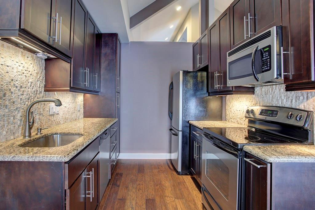 Updated cabinetry with modern hardware, granite counter tops and stone back splash are a beautiful touch to this galley kitchen. New appliances are included.