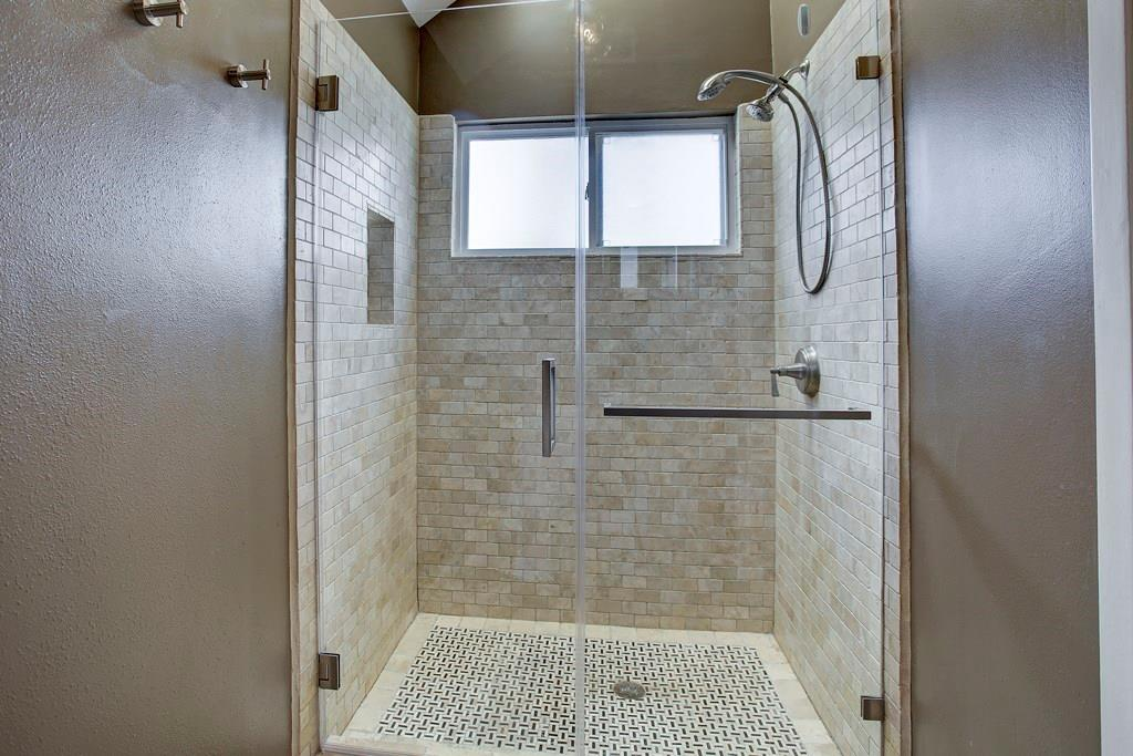 Master bath features updated tile shower, recent neutral paint and ample storage.