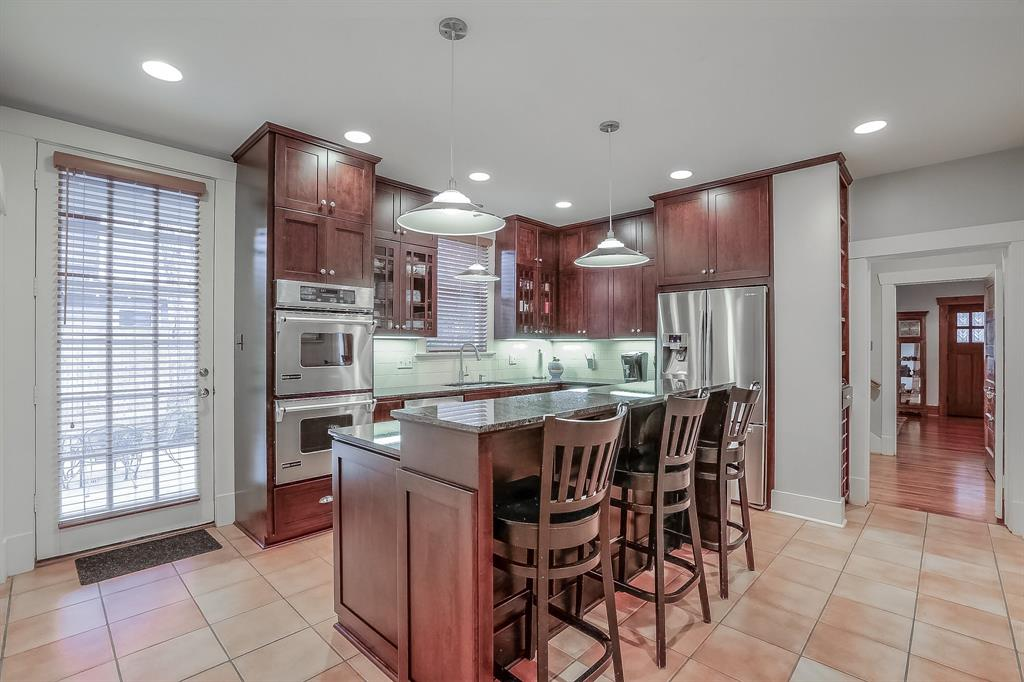 Center-island kitchen with recently refinished cherry cabinets, stainless steel appliances and marble counter tops.