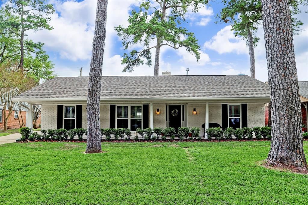 One story, ranch style home with welcoming front porch and painted brick exterior.