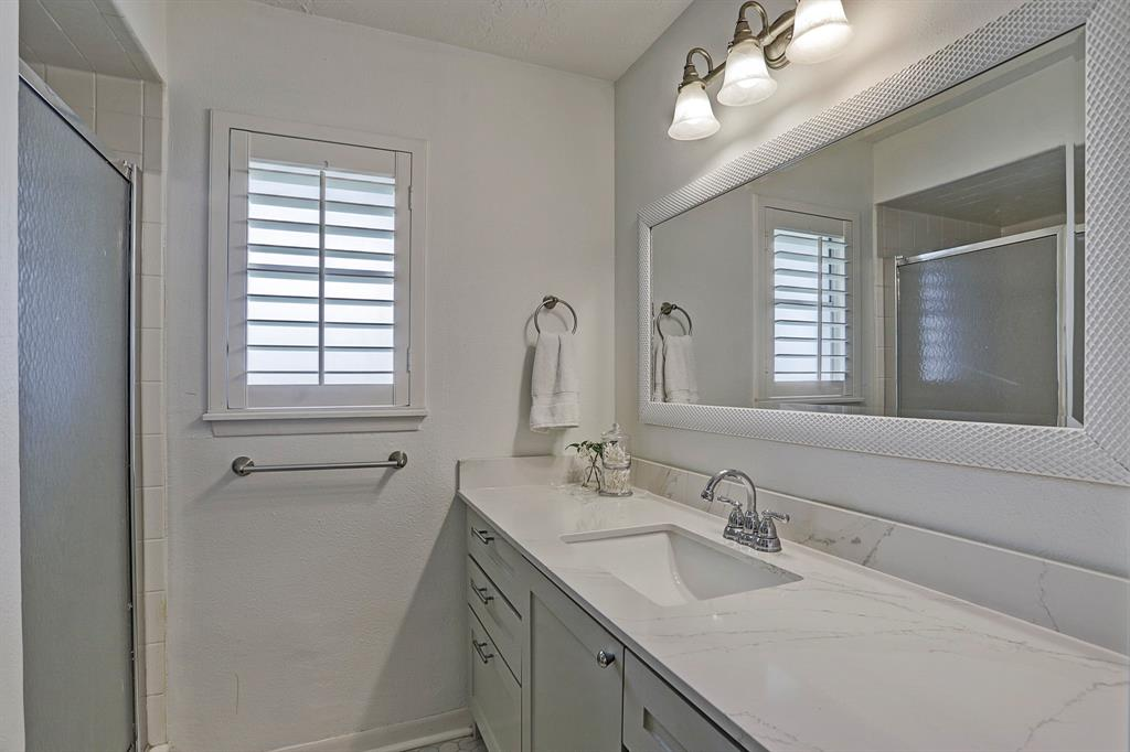 Master bathroom features a walk-in shower, hexagon marble floors, quartz countertops and white paint.