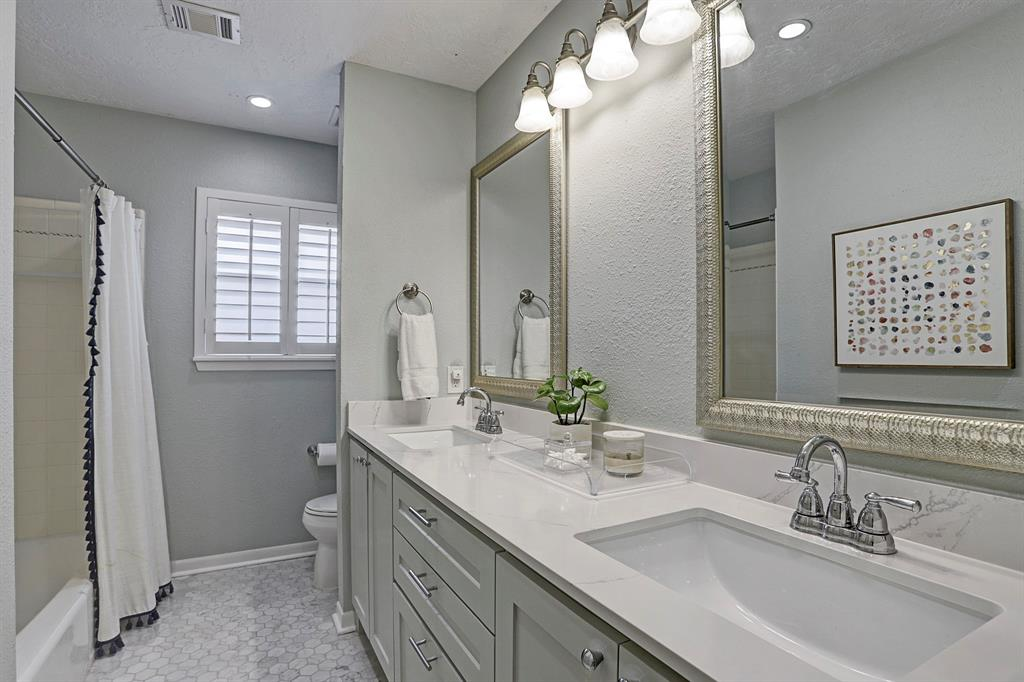Hall bathroom features hexagon marble floors, and double sinks with quartz countertops.