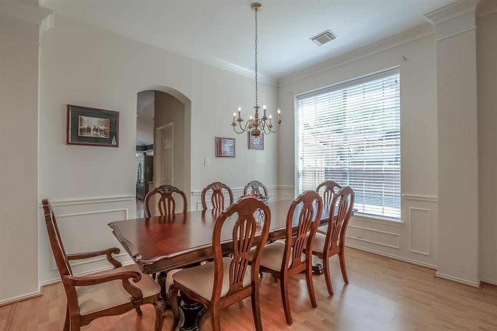 Dining room features wainscoting and crown molding.