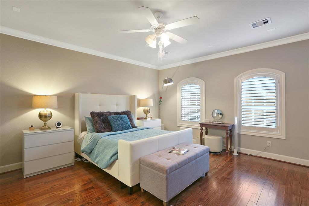 Spacious first floor bedroom with wood floors, crown molding and plantation shutters.