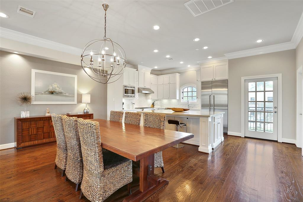 Large dining space that can easily fit an 8-person dining table features an upgraded chandelier.