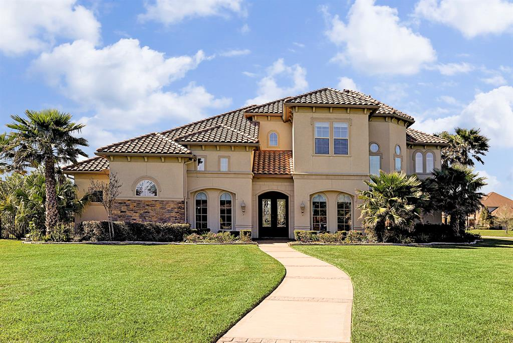 Mediterranean Custom built home on corner, 1 acre lot, in the heart of Katy, in a manned guard gated community, on lake. Truly a RARE find to get a detached approx 900 sq ft FULL GUEST HOUSE.  Main house has four bedrooms with two on main floor, 2 bedrooms upstairs, all have en-suite bathrooms and walk in closets!  Both Game and Media Room, and FOUR car garage with large storage space above.  Media Room can be a bedroom, with a window, closet, and full bathroom. Gourmet kitchen with instant hot water at the sink and large pantry! Custom touches throughout the home include 2 staircases, 3 fireplaces, wine grotto, formal dining room with butlers pantry over 100 LED recessed lights!  There is a balcony on the 2nd floor overlooking the lake so you can enjoy beautiful sunsets.  Tons of extra yard space!  House is stucco and stone with tile roof.   Backyard oasis with large pool with, waterfall,  oversized heated jetted spa & slide. NO FLOODING in Harvey. Low Taxes and no MUD taxes!
