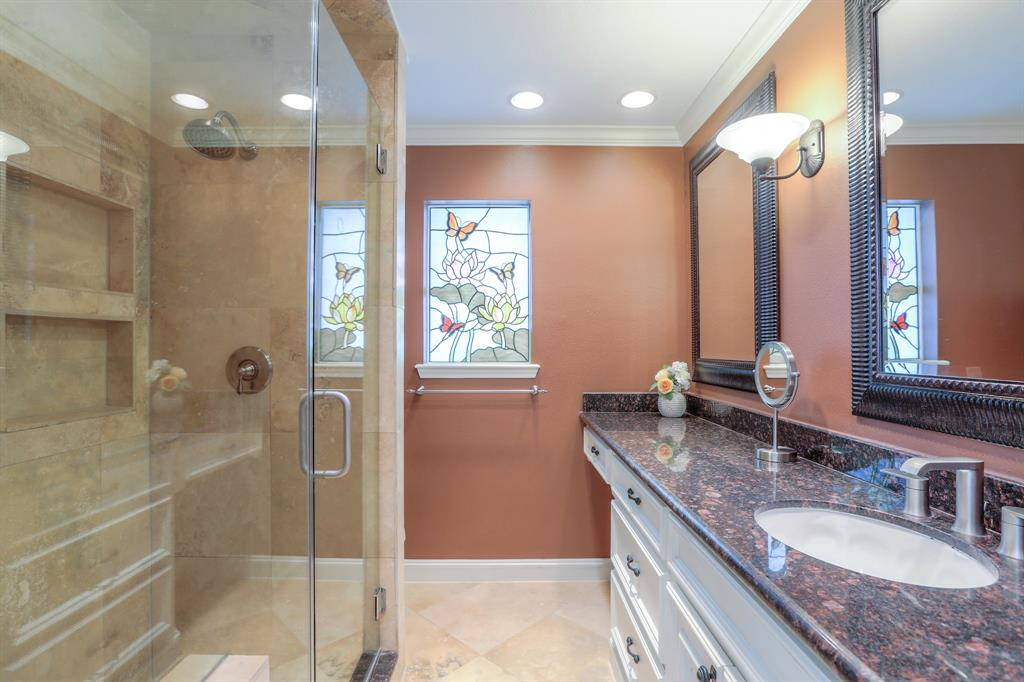 The master bath features updated tile, granite counter top, glass shower enclosure, and an updated faucet.
