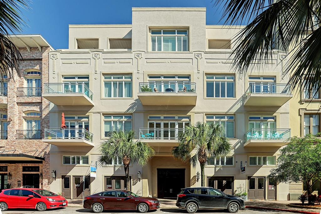 Upscale, modern, 2nd floor condo in Galveston's Historic Strand District features a 128-sq ft balcony clad with travertine and overlooking renowned Post Office Street. Formerly the JC Penny building, the condo provides central location to walk to Galveston's best shopping, dining, & entertainment. One of smallest units in the complex & one of the few offering a balcony, homeowners enjoy exceptional views, including partial views of harbor & cruise ships. Brimming w-light from expansive Anderson double-pane patio doors, the fine condo delivers high ceilings, exquisite hardwood floors, partially bricked accent wall preserved from original Penney's building, granite counters & fire sprinkler system.  Open floor plan w-neutral designer paint palette creates comfortable ambiance. Building provides maximum security w-coded entry flowing into beautiful atrium foyer. Convenient parking, elevator access, private storage make ideal vacation, starter, or  home. Great for med students!