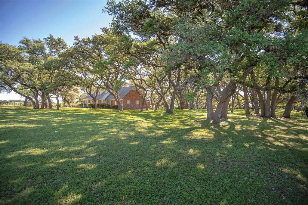 Once in a life time opportunity to own ±310.23 acres on scenic highway FM 390's historic La Bahia Trail.  The La Bahía was originally an east-west Indian trail in southwestern Louisiana and southeastern Texas and eventually extended to Washington-on-the-Brazos and Goliad. In 1830 Henry Austin joined his cousin Stephen F. Austin and applied for a 10 League land grant from Mexico and this gorgeous property is part of that grant. The properties elevation is about 490' and has rolling pastures, groves of mature oak trees, stone outcroppings, and incredible views. New Year Creek borders the west side property line. The 3249 sqft. brick home was built in 1962 and features three bedrooms and 2 ½ baths. Two large living areas both feature impressive fireplaces, wood floors, and wood beamed ceilings. Master bedroom and bath down and two bedrooms and bath up. Beautiful swimming pool surrounded by grove of oak trees in park-like setting. Three barns and two water wells. Community water available.