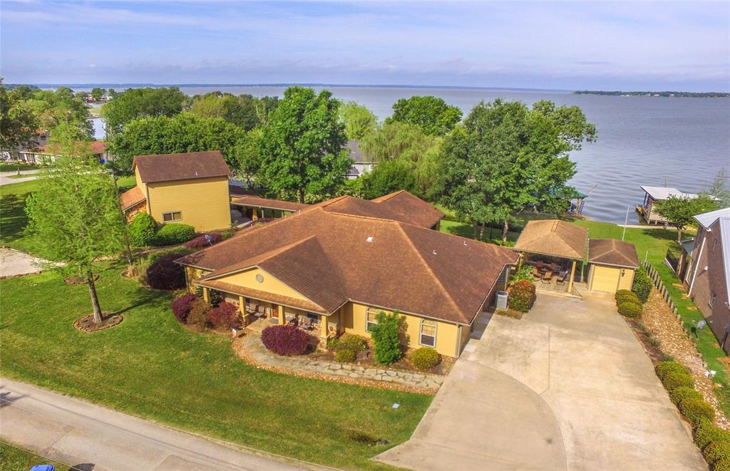 Extraordinary WATERFRONT retreat on 1+ AC. Great Deep Water w/View of Lake most rooms in main house & guest house. Single level main house, apprx 3100 sf, 3 bdrms, 3 baths. Master suite has spacious bath w/spa tub/separate shower (closet is 12x15). Guest suite has private bath & lake view.  Chef's dream kit, Gas 6 burner w/griddle, Sub Zero fridge,  wraparound bar seating joins huge family and game room space w/wall of windows to enjoy lake. Guest house connects by covered walkway, apprx 1700 s.f has 2 bedrooms & full bath, family room w/ kitchenette downstairs, upstairs the 20x22 bunk room w/ b/i bunks for 8 plus ship bed and window seats.  Full bath upstairs. Covered decks, shady/grassy yard, plenty of parking. Boat house for 2 boats & 2 jet skis. Well maintained property, great for weekend or full time home. Must see to appreciate condition & all the extras for entertaining all your friends/family.